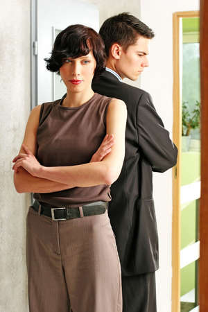 elegant, young couple standing back to back in a room   Stock Photo