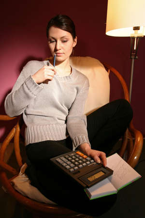 girl, young woman sitting in armchair with notebook on her laps photo