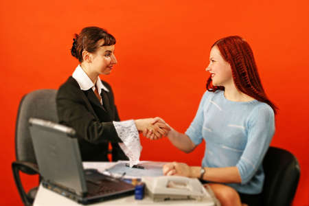two young woman shake hands in work environment Stock Photo - 679669