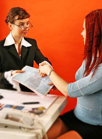 ambiente laboral: Dos j�venes mujer de la mano en medio de trabajo