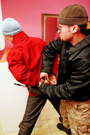 handcuffing: Bodyguard in a black jacket arresting and handcuffing an offender. Stock Photo