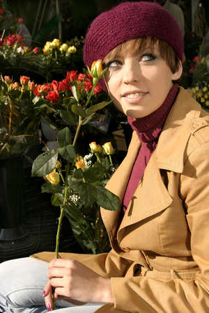 Fashion friendly smiling girl portrait outdoors buying roses. Stock Photo
