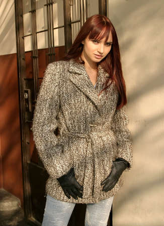 Young beautiful  girl with brown hair standing at a wall, with romantic look.