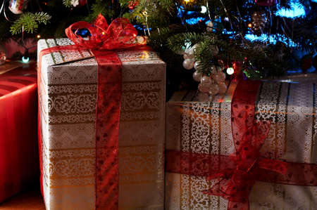 Two christmas gifts under the christmas tree with a red ribbon.