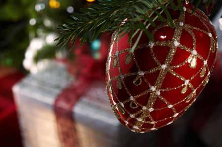 Christmas gifts under the christmas tree with a red bauble in a foreground Stock Photo