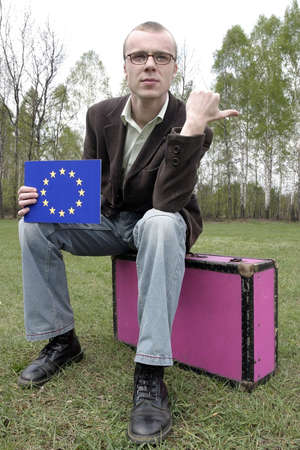 Student hitch-hiking with a european union sign on a board and sitting on a suitcase.
