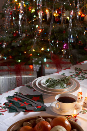 Christmas traditionally decorated table with a cup of borsch and presents in background.