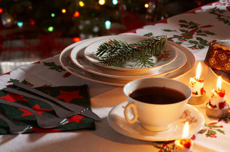 Christmas traditionally decorated table with a cup of borsch with candels.