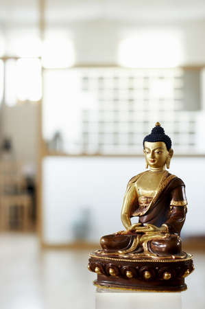 Golden and brown statue of buddha - shallow focus, on a blured background.