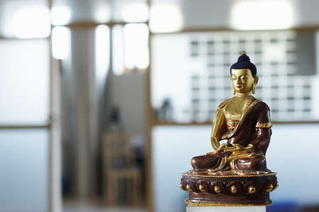 Golden and brown statue of buddha - shallow focus on a blured background.