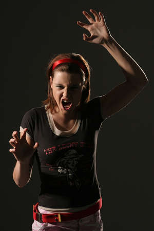 Young angry girl in a deep shadow screaming on a black background.