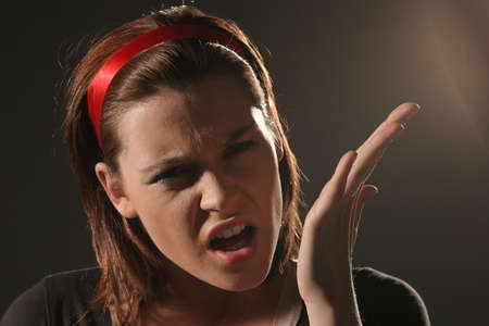 Young angry woman in a deep shadow gesticulating on a black background.