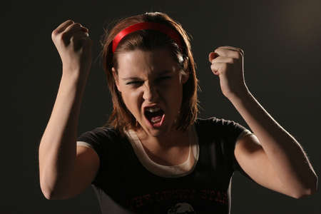 Young angry woman in a deep shadow screaming on a black background. Stock Photo - 2180077