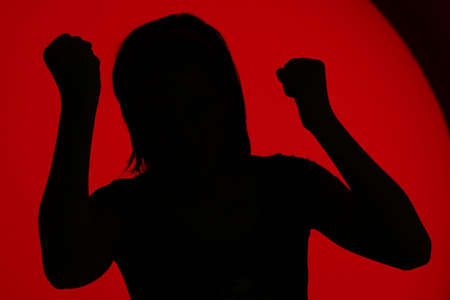 Profile of angry girl with clenched fists on a red background
