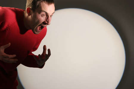 Young man in red pullover screaming and gesticulating - with a white circle in the background. Stock Photo - 2180028