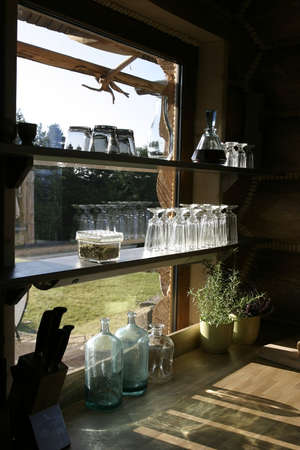 Empty stylish glasses and bottles on a shelf at a window in country side house. Stock Photo