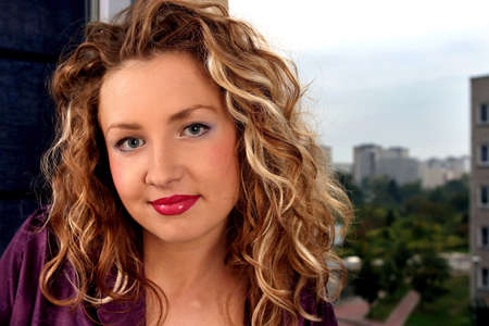 Young beautiful blonde woman with curly hair smiling.