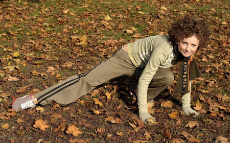 A young woman with a scarf stretching in a  park after a long run.