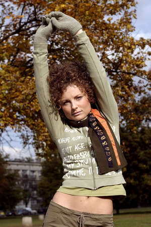 A young woman in a scarf stretching in a  park after long run.