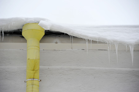 damaged roof: downpipe and icicles on the roof