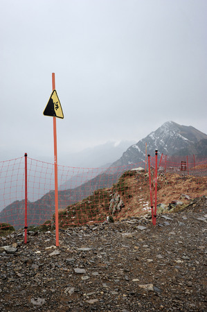 hazardous area sign: sign danger of falling from a height on top of the mountain rose peak 2320 m in Rosa Khutor, Sochi