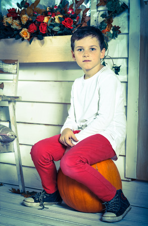 red jeans: little boy in red jeans and a white jacket and sneakers sitting on a pumpkin Stock Photo