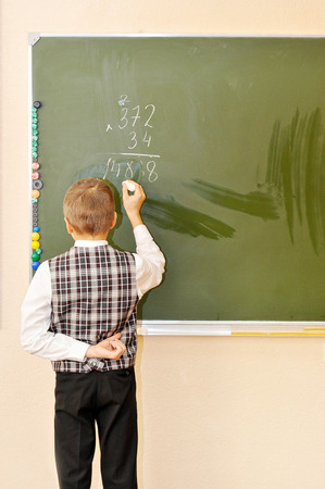 solves: student solves an example and writes it in chalk at the blackboard Stock Photo