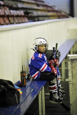 rival rivals rivalry season: St. Petersburg, Russia, 5 January: little hockey player in training sitting on the bench on JANUARY 5, 2015, Saint-Petersburg, Russia