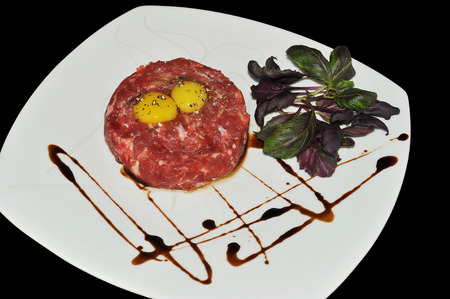 alcaparras: Steak tartar. carne picada y huevo crudo con hierbas y especias en un fondo de mármol, vista desde arriba