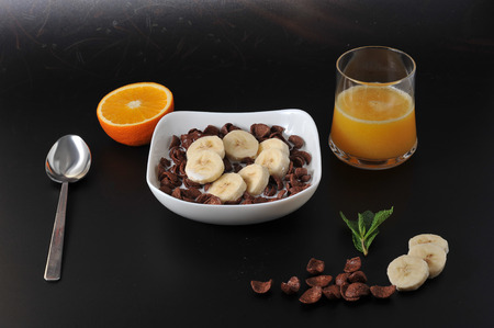 chocolate cereal: healthy Breakfast - chocolate cereal with banana and milk and oranges. top view