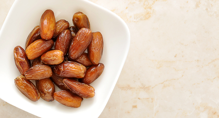 Dried dates fruit in a bowl, on a marble background. top view. copy space