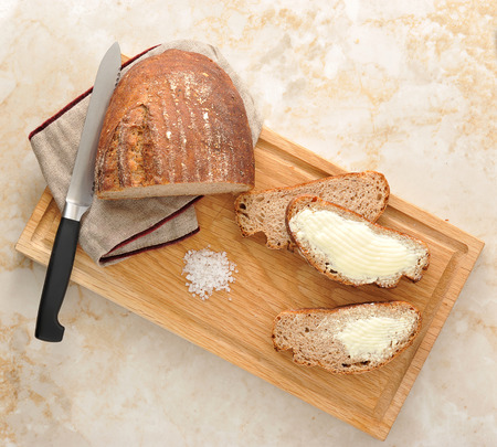 anointed: rye bread on the Board. bread cut into pieces and anointed with oil. the knife and wooden Board. top view Stock Photo