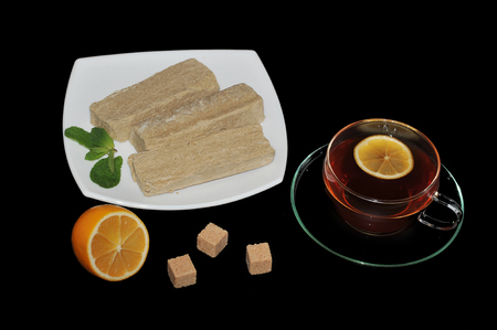 confect: halva on a white plate - Oriental sweets. tea in a transparent mug with a slice of lemon.  mint and cubes of cane sugar on black background. top view Stock Photo
