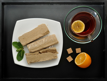 confect: halva on a white plate - Oriental sweets. tea in a transparent mug with a slice of lemon.  mint and cubes of cane sugar on black tray background. top view