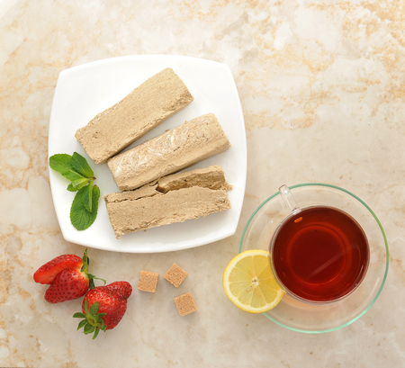 confect: halva on a white plate - Oriental sweets. tea in a transparent mug with a slice of lemon. strawberry, mint and cubes of cane sugar. top view