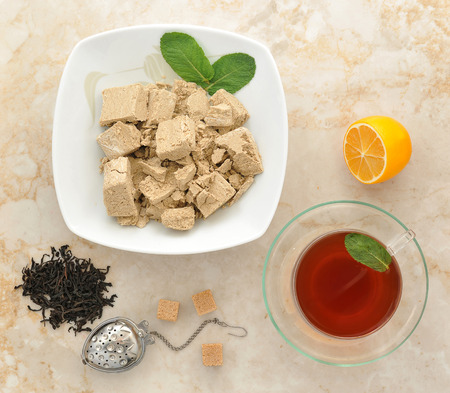confect: Eastern sweets - halva in a plate with mint leaves. black tea in a transparent mug with mint. dry black tea leaves, teapot, spoon, sugar cubes on marble background. top view Stock Photo