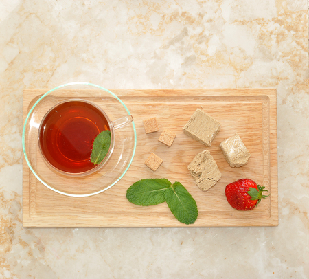confect: Oriental sweets - halva on wooden plate with mint leaves and strawberry. black tea in a transparent mug with mint. top view
