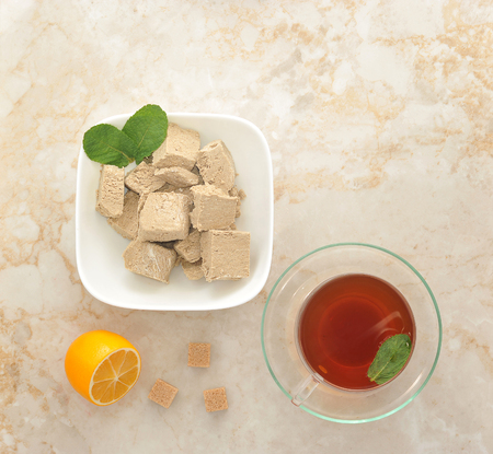 confect: Oriental sweets - halva in a plate with mint leaves. black tea in a transparent mug with mint. sugar cubes and lemon on marble background. top view
