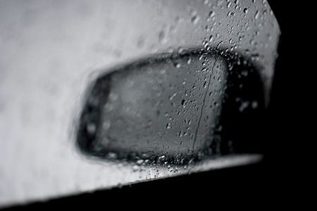 rear view mirror of the car. view through glass with raindrops. abstraction