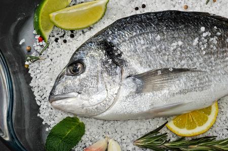 dorado fish: Dorado fish is in glass dish with salt, rosemary, garlic, lime and lemon.
