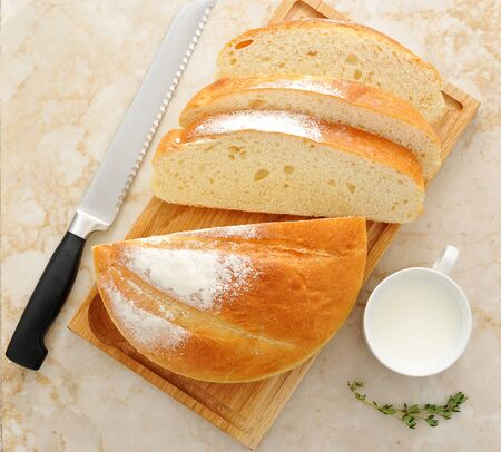 bread knife: white round bread cut into slices with a mug of milk on wooden Board on a marble background. bread knife. top view Stock Photo