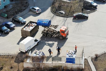 camion de basura: San Petersburgo, Rusia - 28 de marzo, 2016: cami�n de la basura se acumula la basura en el patio de una casa