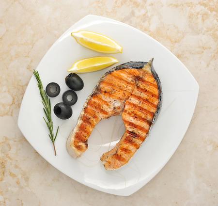 gegrilde zalm steak met olijven, rozemarijn, citroen op de plaat. bovenaanzicht Stockfoto