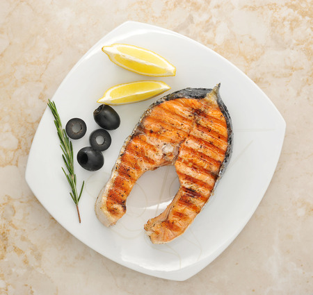 grilled salmon steak with olives, rosemary, lemon on the plate. top view