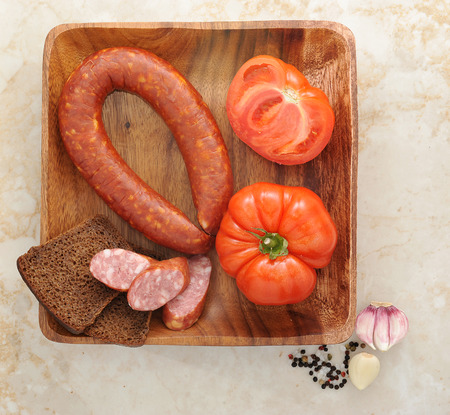 krakow sausage: Krakow sausage, tomatoes and black bread on wooden plate. top view