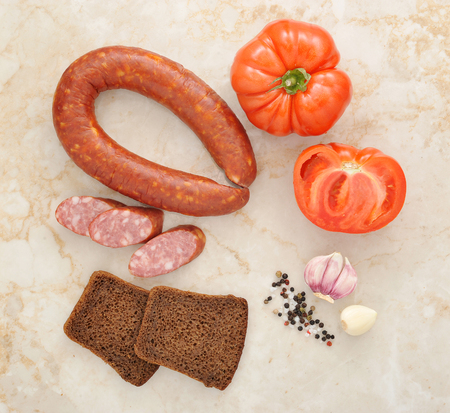 krakow sausage: Krakow sausage, tomatoes and black bread on a marble background. top view