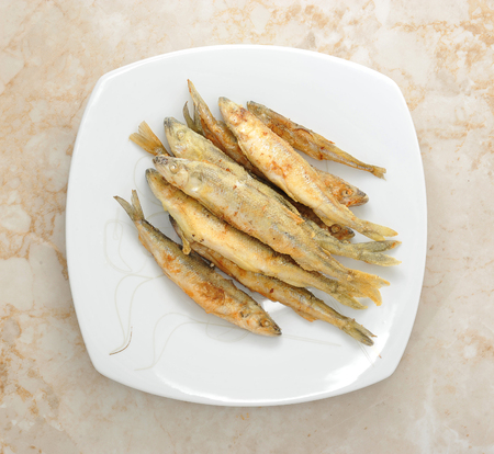 textille: fish smelt  fried in a plate. top view