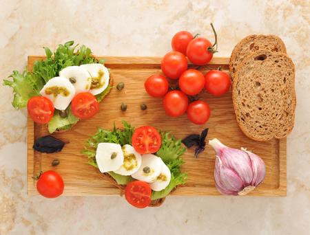 alcaparras: Mozarella con los tomates en una tabla de madera. vista superior Foto de archivo