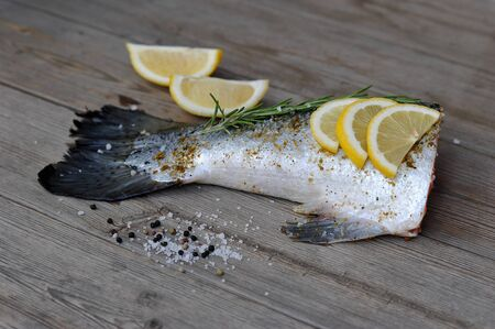 lies: fishtail salmon marinated with lemon and rosemary on wooden background Stock Photo