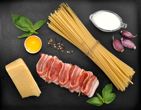 cream cheese: set of products for pasta Carbonara - spaghetti, bacon, cream, Parmesan cheese, Basil, egg, garlic, spices - on black background, top view